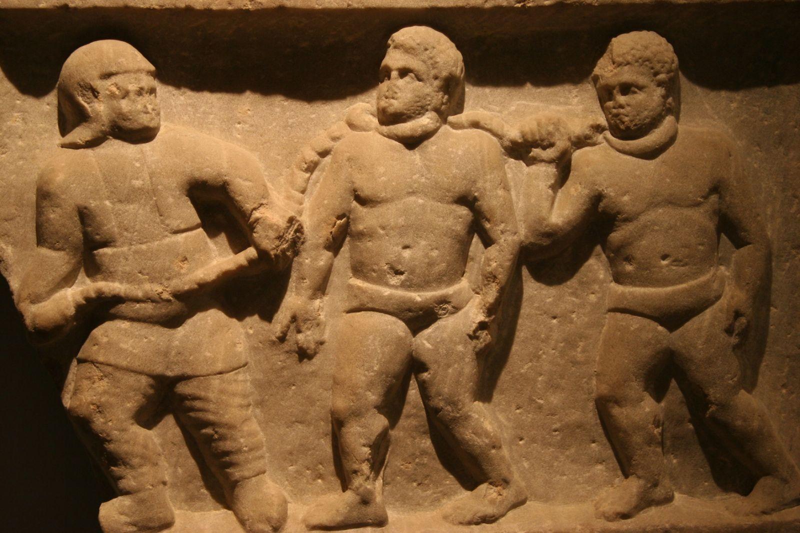Płaskorzeźba przedstawiająca mężczyznę prowadzącego na łańcuchu przyczepionym do ich szyj dwóch niewolników.