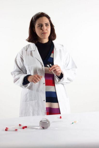 Une femme en blouse blanche qui tient une éprouvette