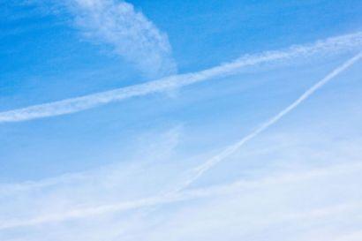 Ciel bleu avec des trainées de suies laissées par les avions