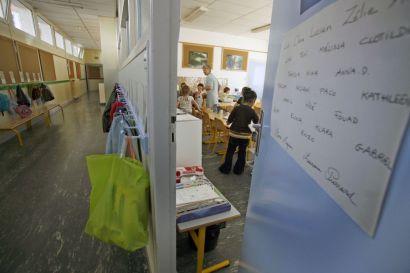 Vue sur une salle de classe depuis une porte entrouverte dans le couloir