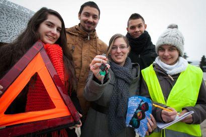 Les étudiants organisateurs posent avec un triangle de signalisation, des clés de voiture et un gilet jaune fluo