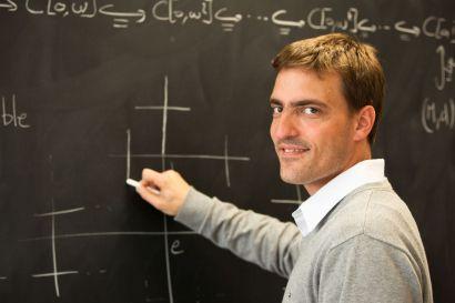 Un jeune homme tenant une craie devant un tableau avec des symboles mathématiques