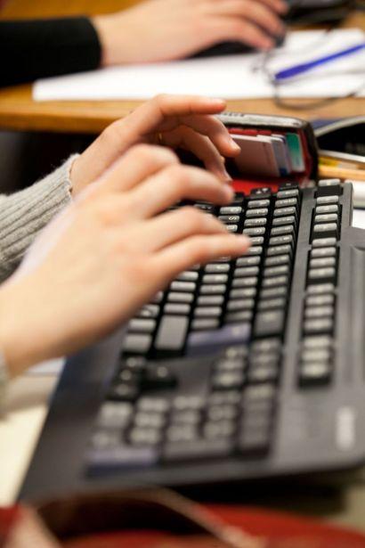 Des mains tapant sur un clavier d'ordinateur