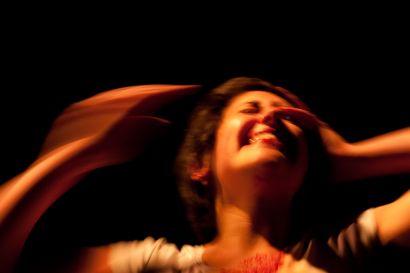 Visage d'une femme souriante floue, elle a une main sur une tête et l'autre qui va se poser dessus.