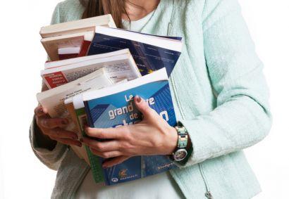 Une étudiante avec une pile de livres dans les bras