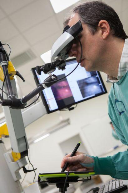 Un chirurgien regarde dans un appareil.