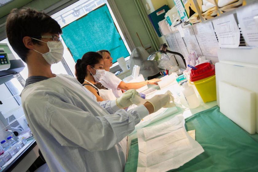 Un homme et deux femmes en blouse, portant des masques, en train d'enfiler des gants en latex et de préparer du matériel stérile.