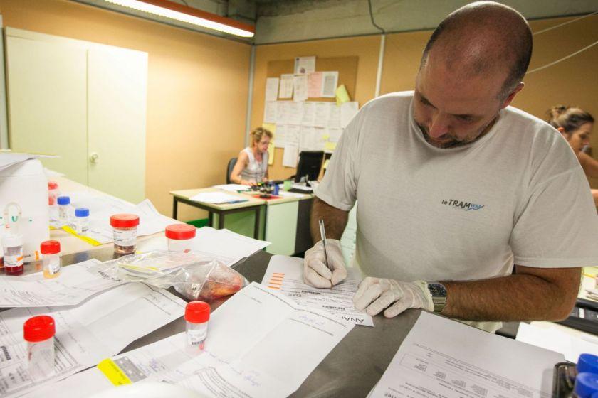 Un homme en train de noter des chsoes sur un papier, autour de lui les flacons contenant les prélèvements.