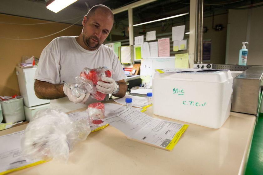 Un homme portant des gants en train de réceptionner des boites contenant des prélèvements biologiques. Il a un stylo dans la main et il y a des feuilles sur le plan de travail devant lui.