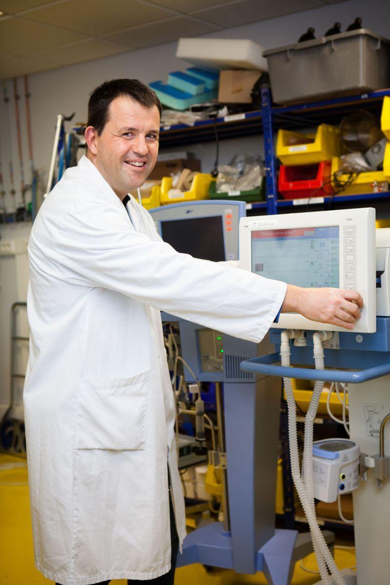 Un homme pose devant une machine au service biomédical du CHU.