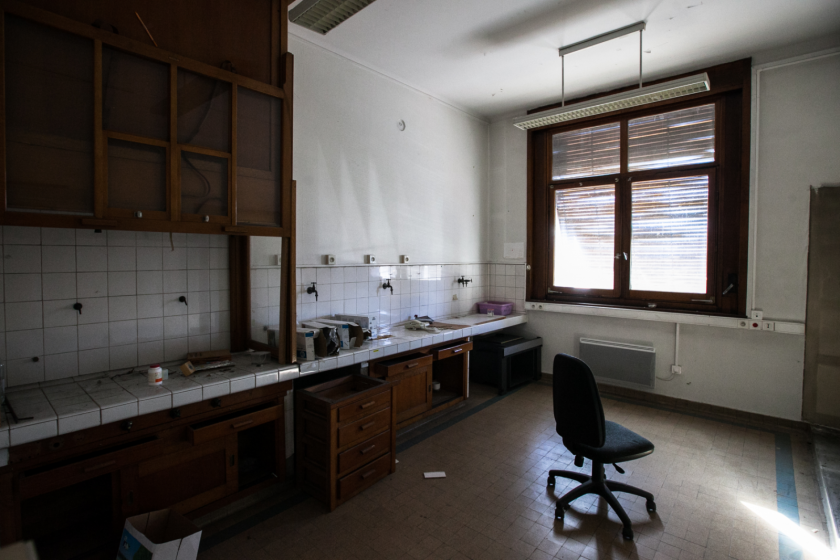 Une salle vide avec d'anciennes paillasses et une hotte en bois.