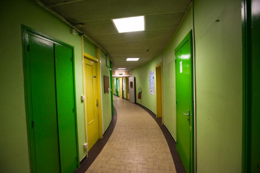 Vue sur un couloir arrondi avec des portes vertes et jaunes.