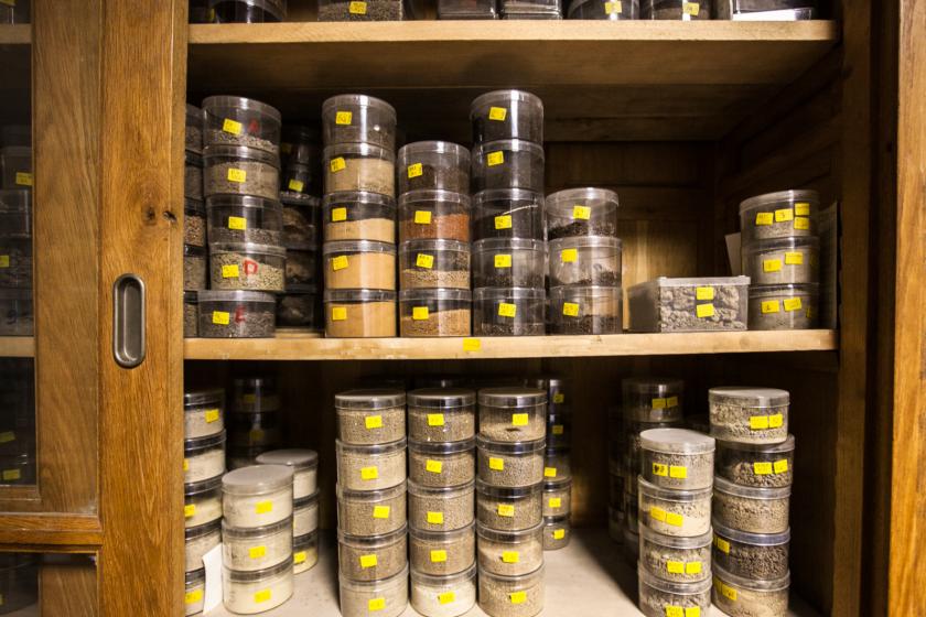 Dans un meuble en bois, de petits boites transparentes remplies d'échantillons de sols de toutes couleurs.