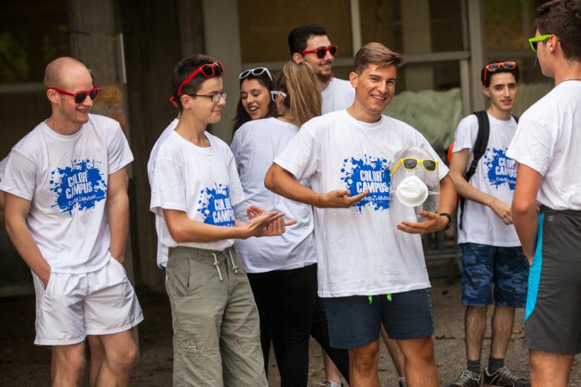 Des étudiants tous équipés du même tee shirt blanc montrent leur tee-shirt