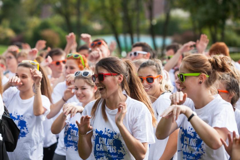 Un groupe d'étudiantes très souriantes avec lunettes de soleil colorées et toutes le même tee shirt