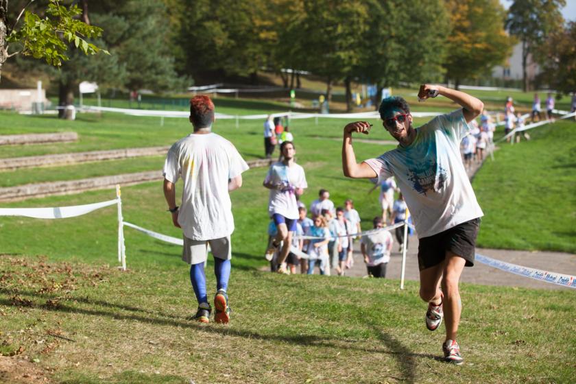 Une course, l'étudiant en tête couvert de poudre bleue fait signe au photographe