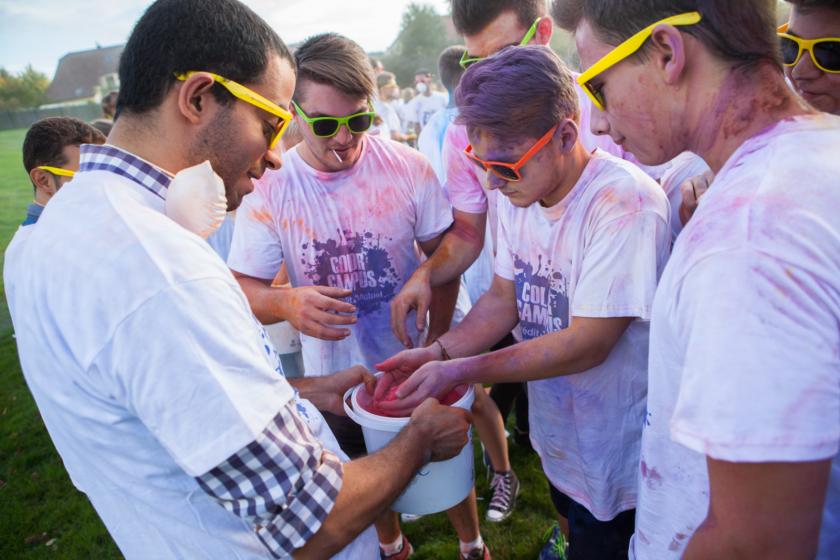 Des étudiants plongent les mains dans un seau de poudre colorée.