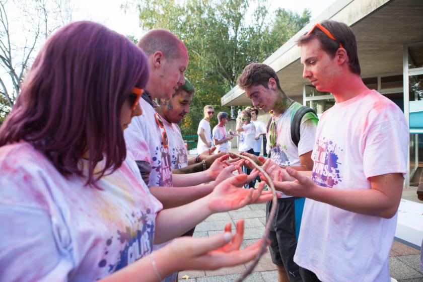 Des étudiants couverts de poudre tiennent une branche en participant à un jeu.