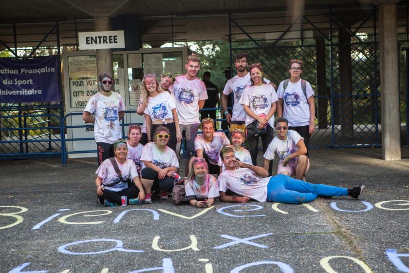 """Un groupe d'étudiants couverts de poudre colorée qui posent devant un marquage à la craie au sol indiquant """"bienvenue aux étudiants"""""""