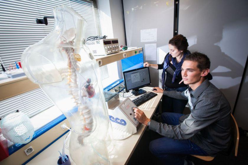 Deux étudiants assis devant un ordinateur à côté d'un mannequin transparent avec un coeur/=.