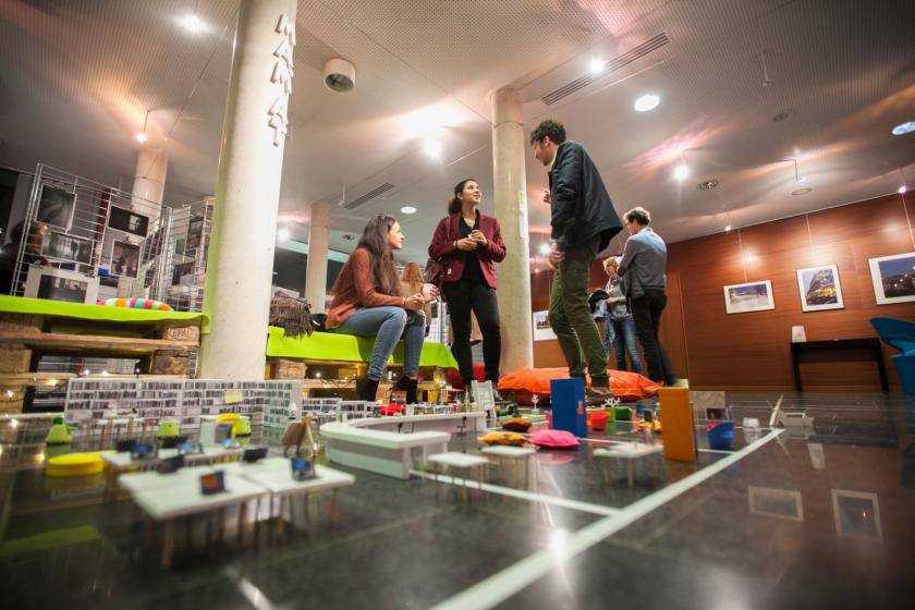Trois étudiants en train de discuter vus en contre-plongée. À leurs pieds, des meubles miniatures évoquant une bibliothèque.