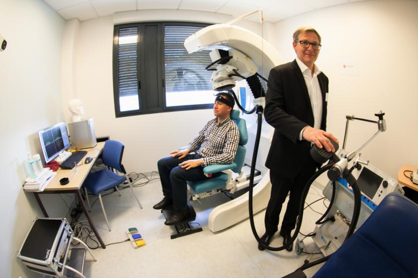 Le dr. Emmanuel Haffen devant un robot de stranscrânienne dans lequel est installé un homme.