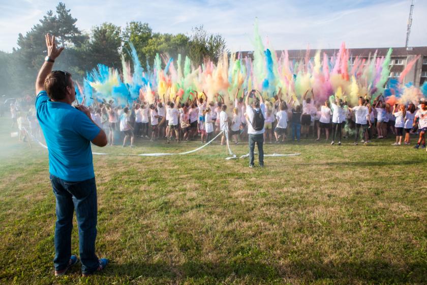 Un grand groupe d'étudiants lance en l'air des nuages de poudre colorée.