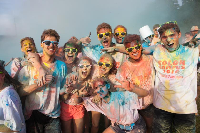 Des étudiants recouverts de poudre colorés en groupe font signe au photographe.