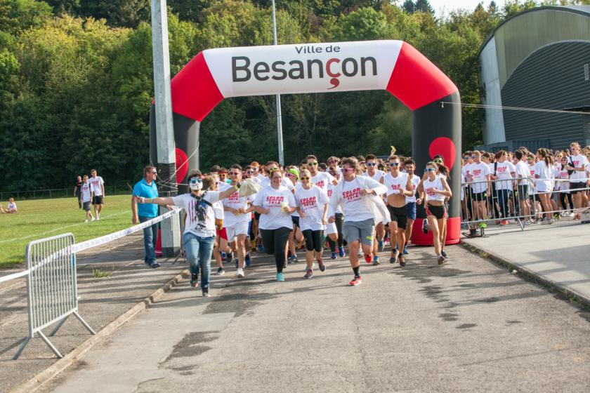 """Départ d'une course sous un portique estampillé """"ville de besançon"""". Les étudiants qui courent portent tous le même tee shirt blanc"""
