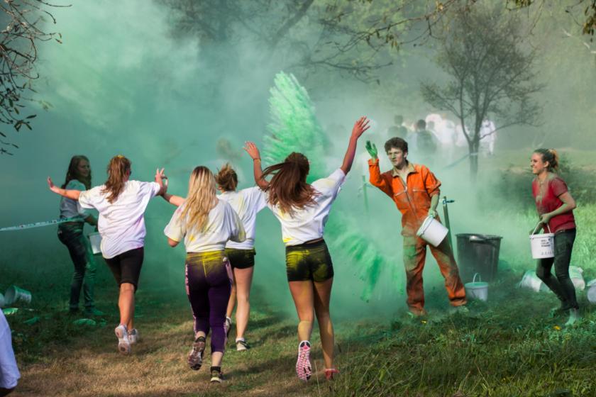 Des filles de dos qui courent et d'autres étudiants qui portent des seaux et qui leur jettent de la poudre verte.