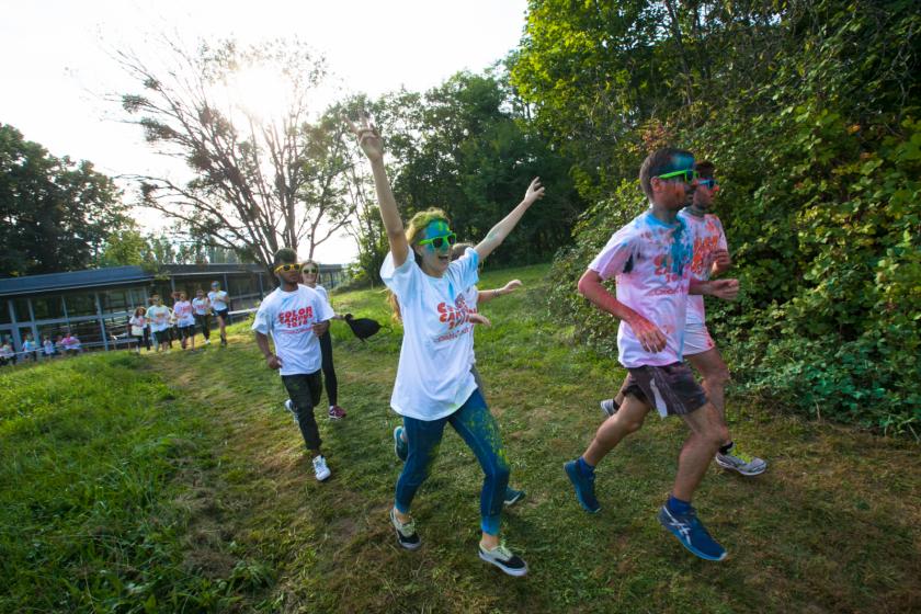 Des étudiants couverts de poudre qui courent, une fille souriante lance les deux bras en l'air.