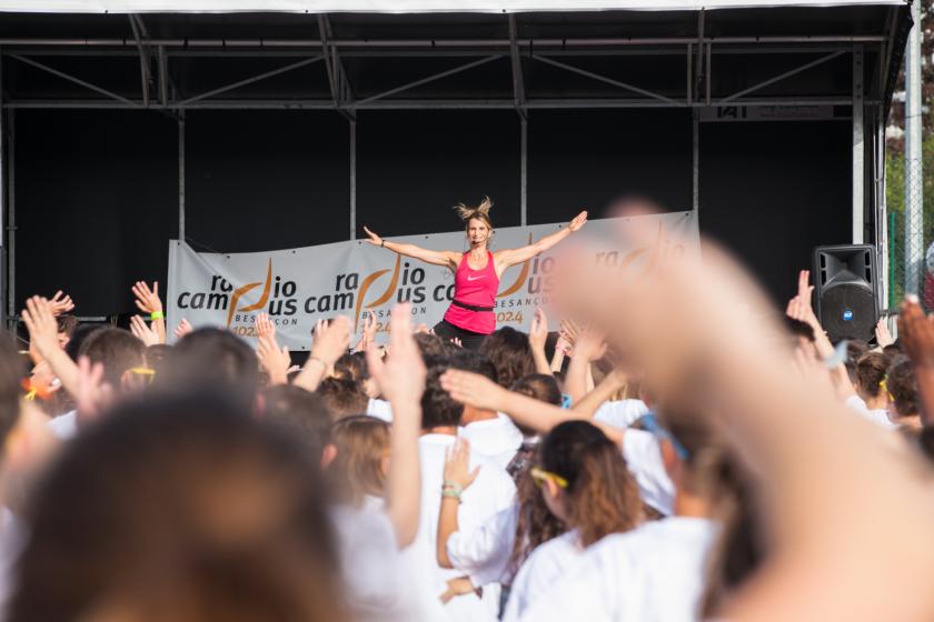 Une femme sur une estrade en tenue sportive avec un micro fait de grands gestes avec les bras