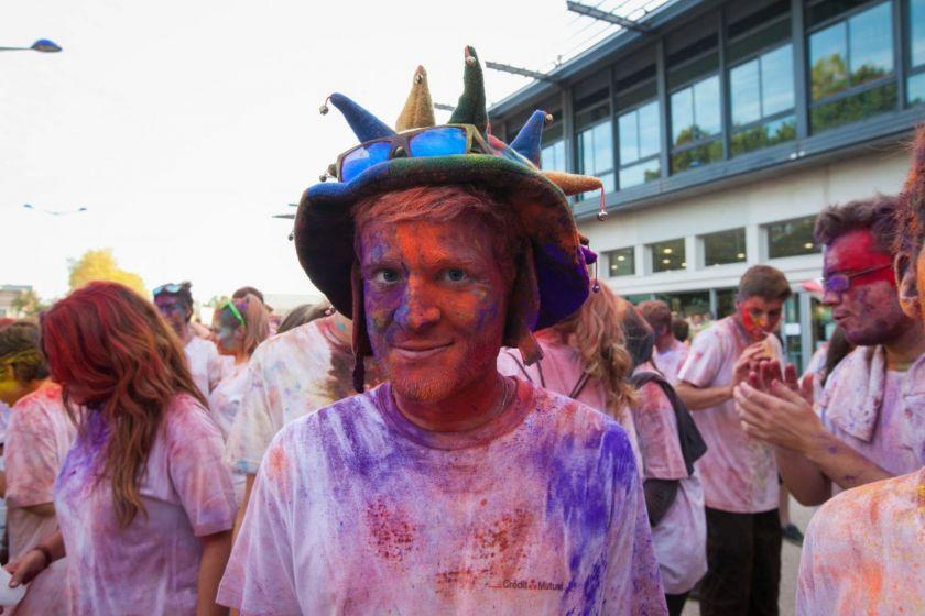 Dans la foule, un étudiant avec un chapeau couvert de poudre colorée.
