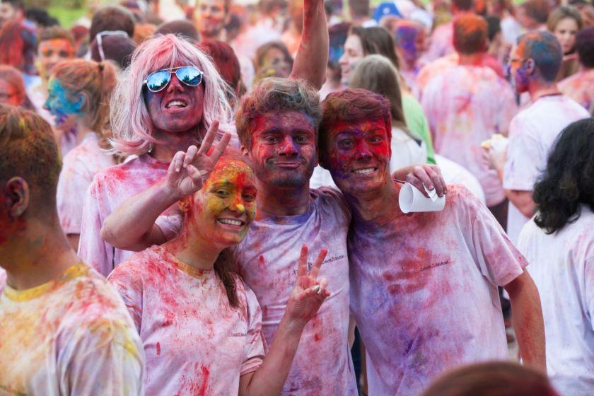 Foule d'étudiants recouverts de poudre colorée. Quatre d'entre eux posent pour l'objectif.