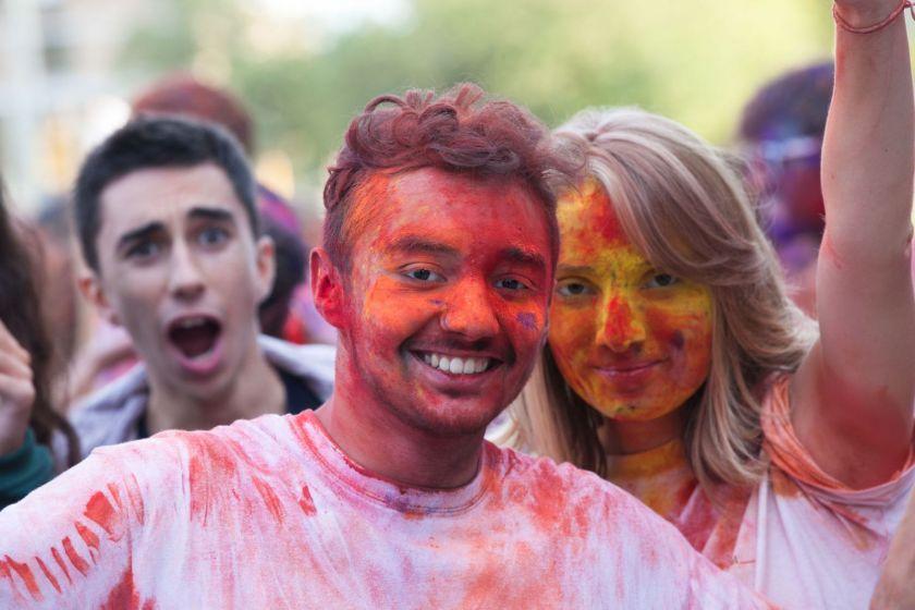 Un jeune homme et une jeune fille souriants et recouverts de poudre colorée.