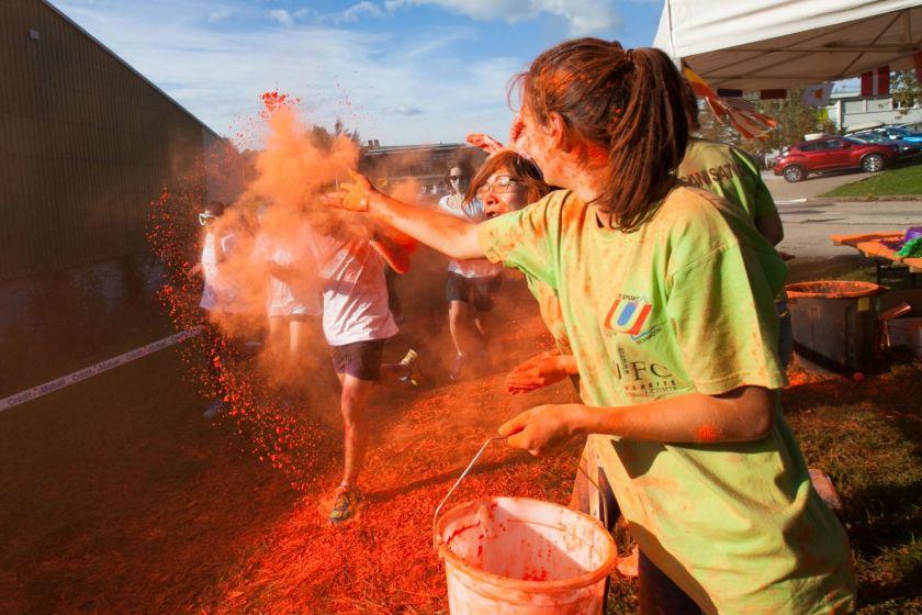 Une jeune fille jette de la poudre rouge sur les coureurs.