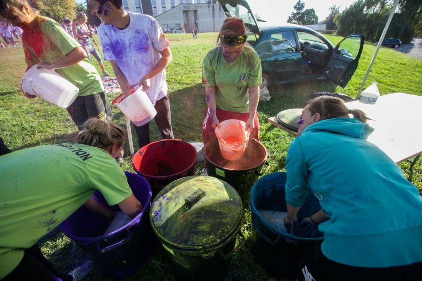 Des étudiants en tee-shirt vert préparent des seaux de poudre colorée