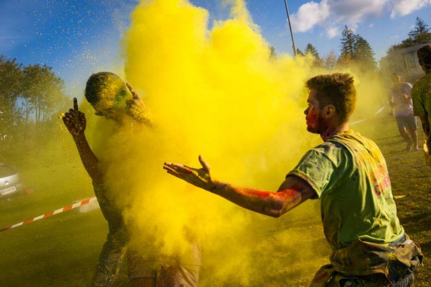 Un jeune homme lance un nuage de poudre jaune sur un coureur.