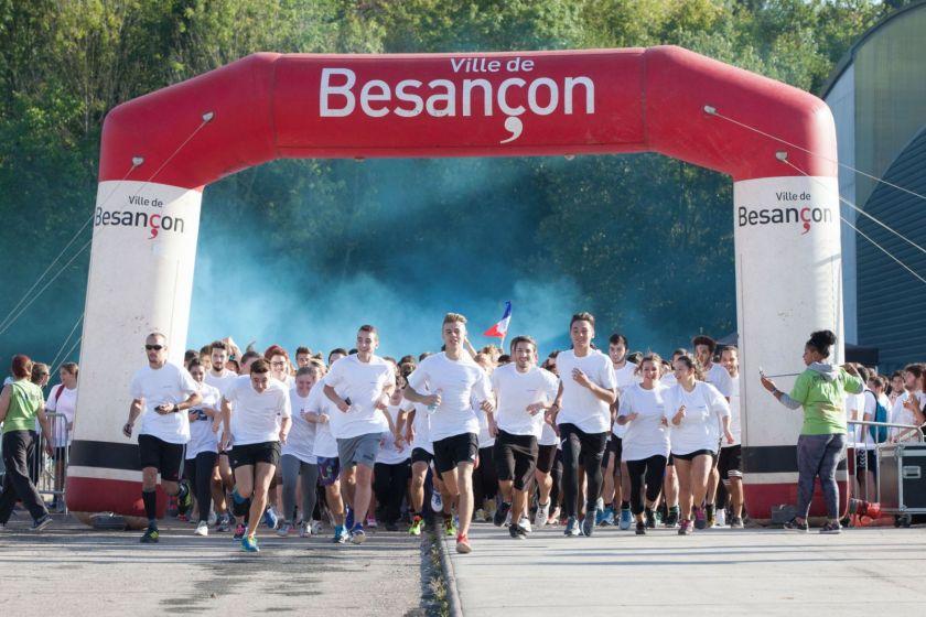Une masse d'étudiants en tee-shirt blancs court. Derrière eux, un nuage de poudre bleue.