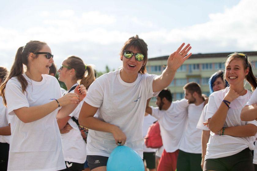 Trois étudiantes en tee-shirt blanc dont une salue le photographe.