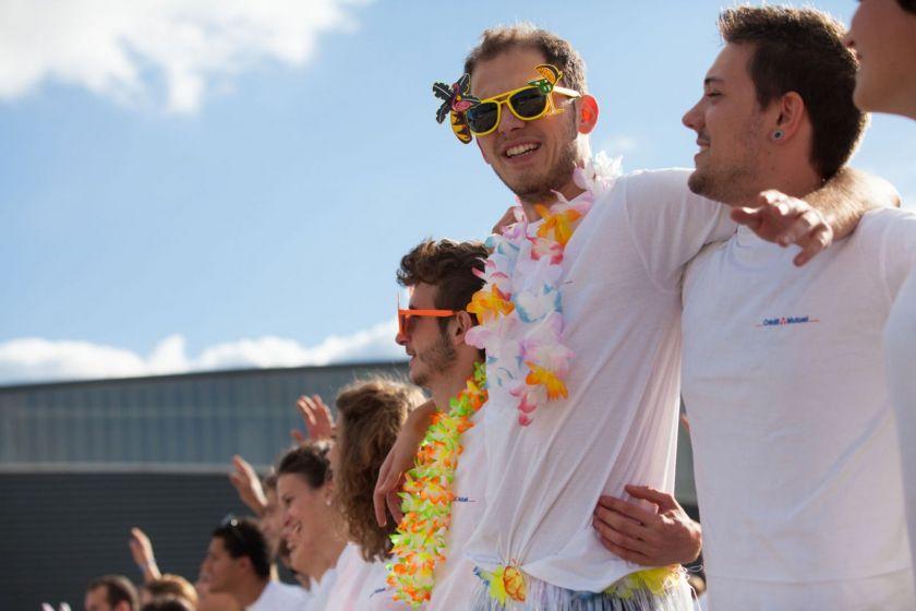 Des étudiants en tee-shirt blanc avec des guirlandes de fleur et des lunettes de soleil décorées sous le soleil.