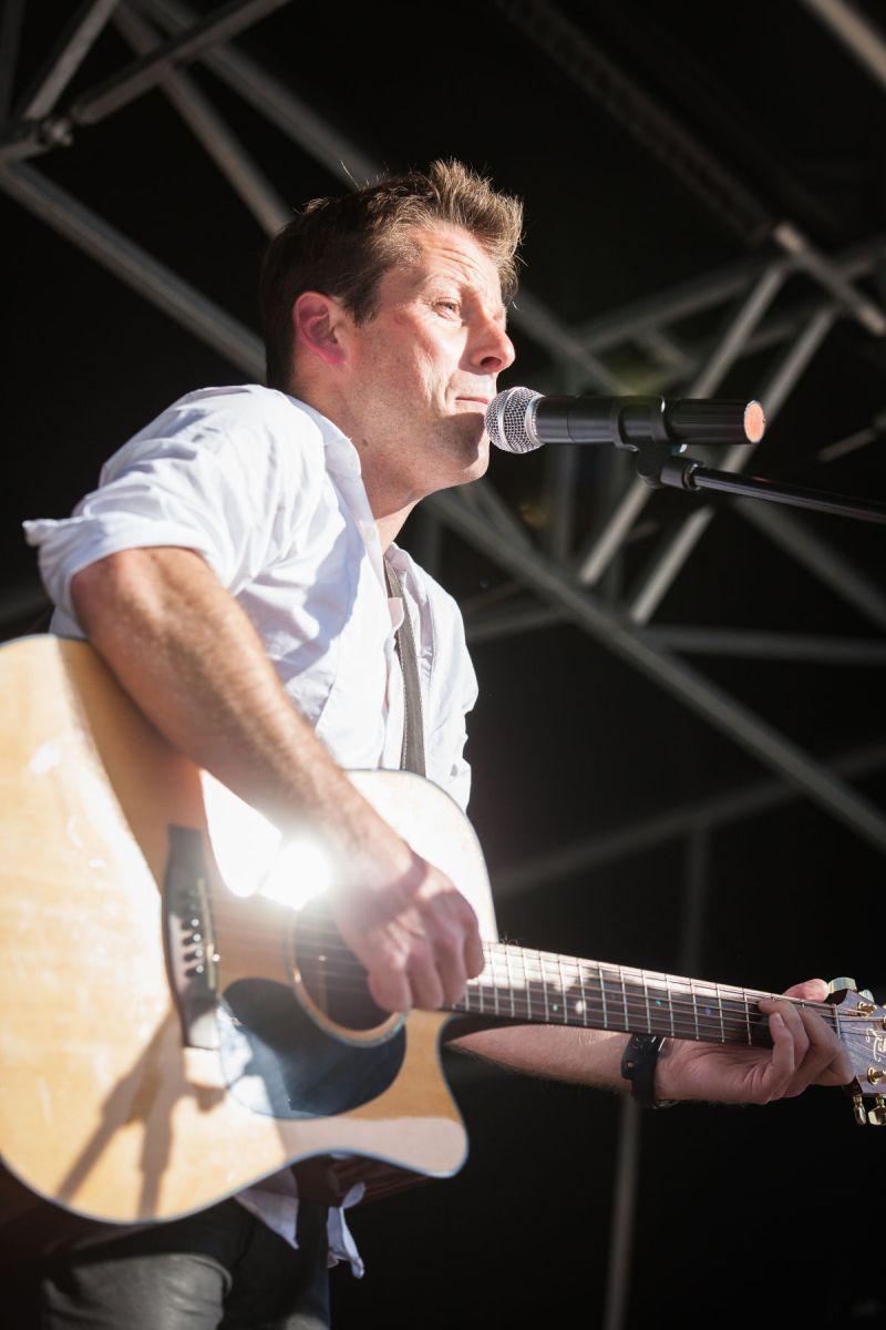 Un homme joue de la guitare et chante au micro.