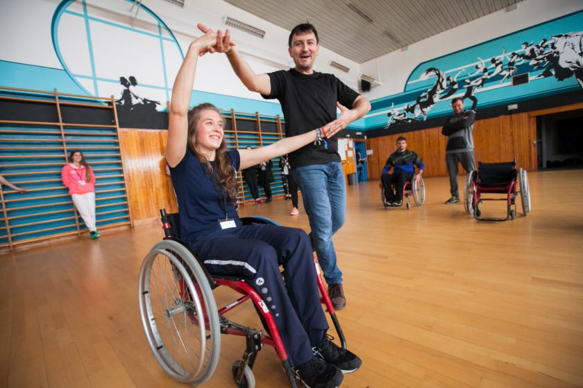 Une jeune fille dans un fauteuil roulant danse avec un homme debout. Ils se tiennet par la main.