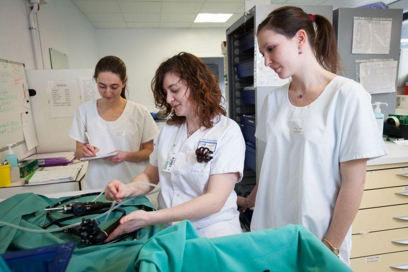 Trois jeunes femmes en blouse blanche à la laverie du service d'endoscopie digestive.