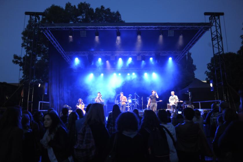 Une scène de concert en extérieur, de nuit, avec des éclairages bleus