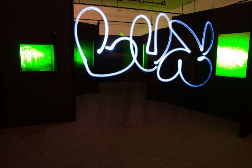 """""""Lux"""" écrit en lightpainting dans la salle d'exposition."""