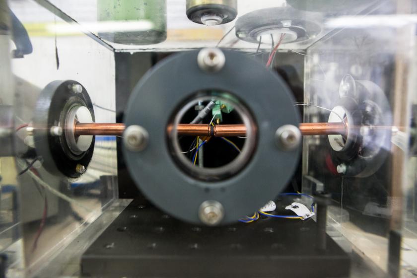 Un cube en plexiglass avec des sortes de hublots à l'intérieur duquel on voit un microcapteur entre deux tiges en cuivre.