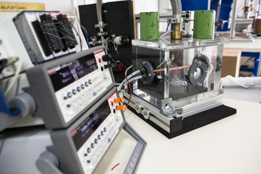 Un cube de plexiglass branché à divers tuyaux et à des appareils de type oscilloscope.