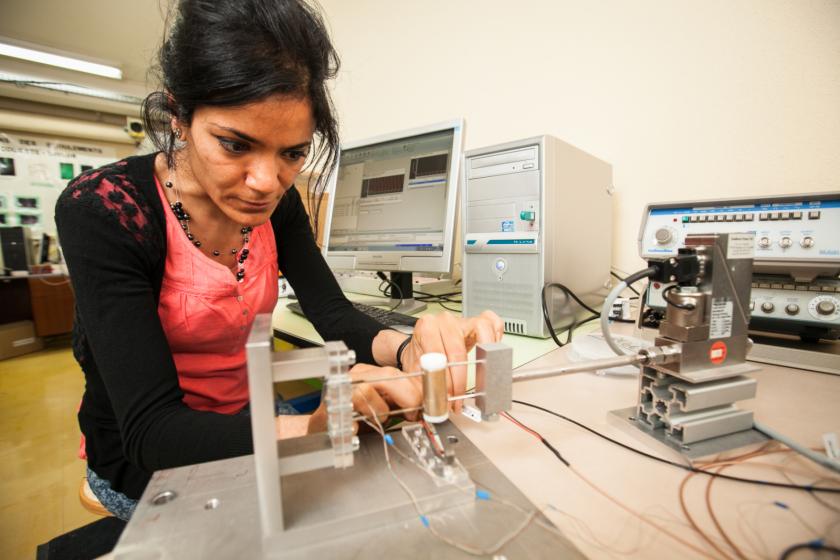 Une jeune femme manipule un banc de caractérisation de microstructures.
