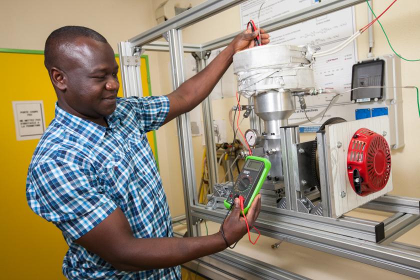 Un homme tenant un voltmètre devant un prototype de moteur stirling.